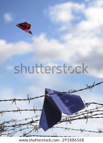 two passports folded as paper planes, the European one is flying in the blue sky, the other one is labeled with refugee and remains trapped in the barbed wire of the frontier, copy space - stock photo