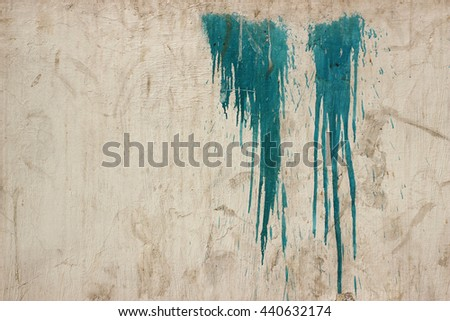 Two patches of dripping blue paint on old textured worn out Indian wall - stock photo