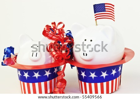 Two patriotic piggy banks sitting in stars and stripes hats.  An american flag is in one of the banks.  White background.