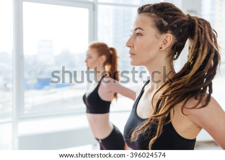Two peaceful attractive young women practicing yoga in studio - stock photo