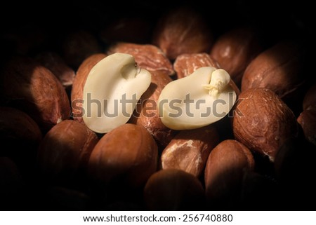 Two peanut half lie among a heap of roasted peanuts on a black background - stock photo