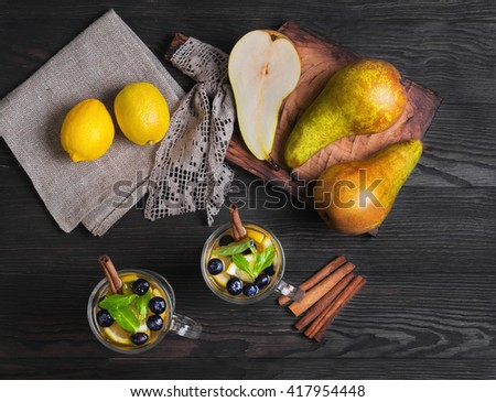 Two pears fruit cocktails in glasses, ingredients for cocktails and fresh fruit whole pears, lemons, blueberries, mint leaves, cinnamon sticks, burlap cloth, wooden board dark background, rustic style - stock photo
