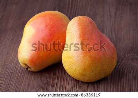 Two pears isolated on a wooden background.