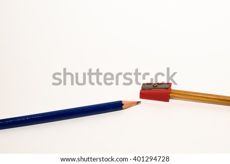 Two pencils and a sharpener depicting the situation of sharpening pencils - stock photo