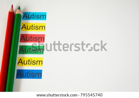 Two  pencils with colorful words AUTISM. Free space for your text
