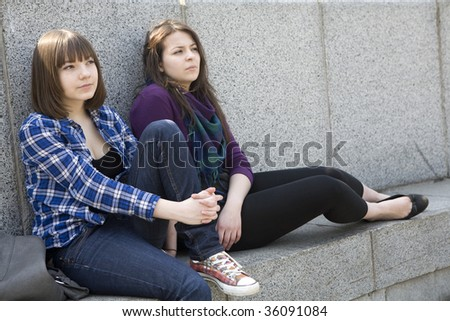 two pensive teen girls sitting at river