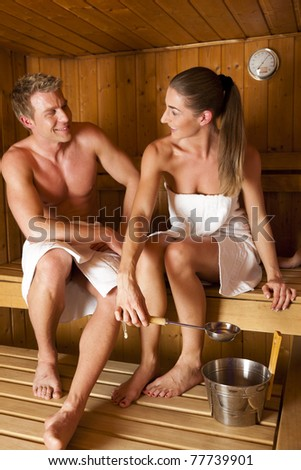 Two people - a couple -  enjoying a hot sauna, having a casual chat - stock photo