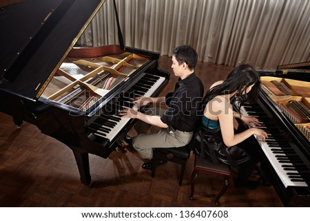 Two people, a couple playing duet musical performance with two grand pianos - stock photo