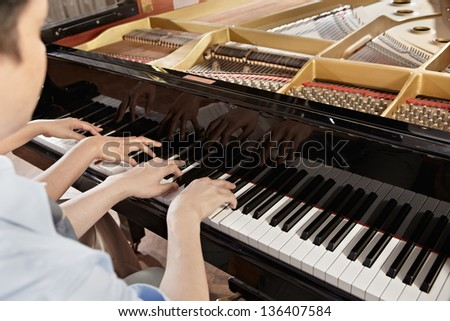 Two people, a couple playing piano duet, showing mostly their hands - stock photo