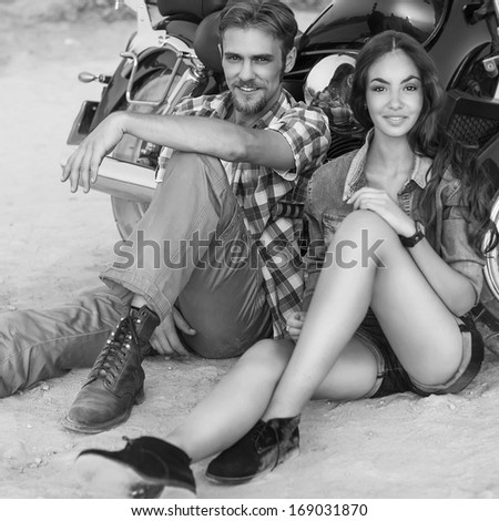 Two people and bike - fashion woman and man sitting by motorbike and resting. Adventure and vacations concept - stock photo