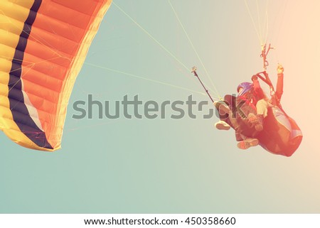 Two people are flying on a paraglider in the sky. Toned - stock photo