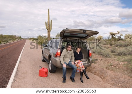 Two people are stranded on the side of a remote desert road out of gas.