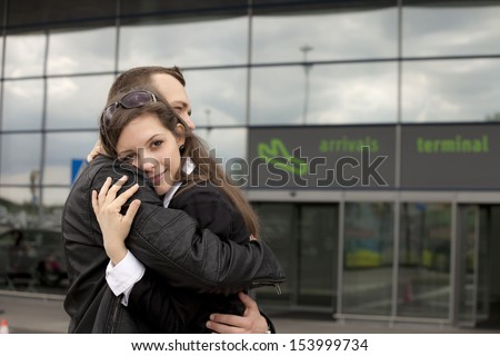 Two people at the airport embracing - stock photo