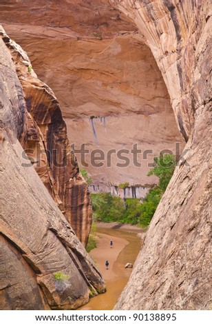 Two people backpack through a narrow canyon in the Utah wilderness - stock photo