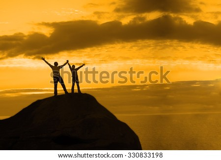 Two people between clouds Full length silhouette of happy couple stand together on peak of a mountain with hands raised up, sunset and ocean. Man and woman on top mountain look at beautiful night - stock photo
