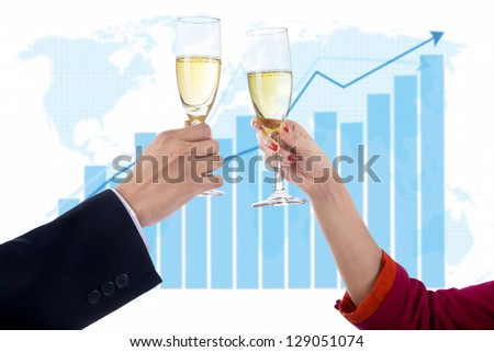 Two people celebrate success with champagne on profit bar chart background - stock photo