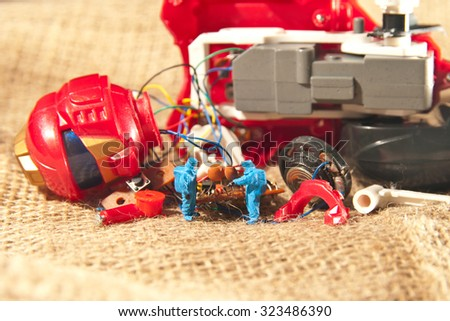 Two people checking broken toy. The concept technology. - stock photo