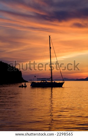 Two people climbing on a sailboat during a gorgeous sunset. - stock photo