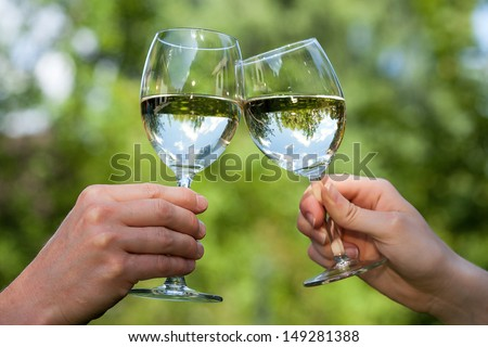 Two people clinking each other's glasses with water - stock photo