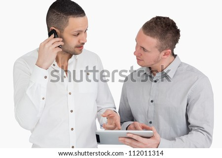 Two people discussing while phoning and holding a tablet computer against a white background - stock photo