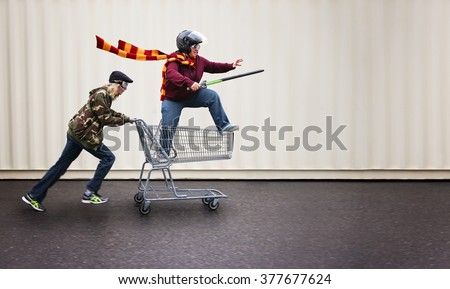 two people dressed up as super heroes or characters horsing around in a shopping cart with goggles and a helmet and sword  - stock photo