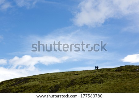 Two people enjoying the view from a hill top