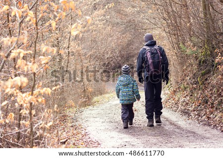 Two people, father and son, walking or hiking autumn or winter forest road, back view.