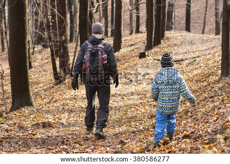 Two people, father and son, walking or hiking in autumn forest, back view.