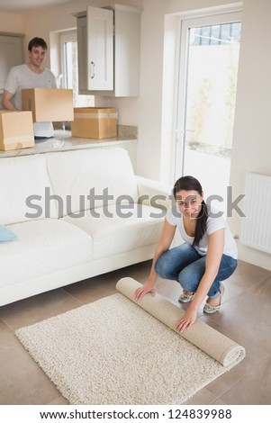 Two people furnishing the house while holding boxes and rolling out a carpet - stock photo