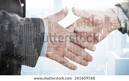 Two people going to shake their hands against city skyline - stock photo