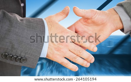 Two people going to shake their hands against room with large window looking on city