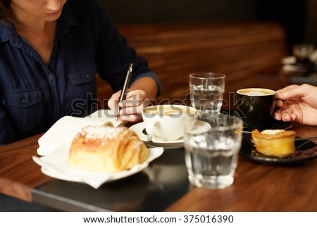 Two people having coffee and pastry at a cafe - stock photo