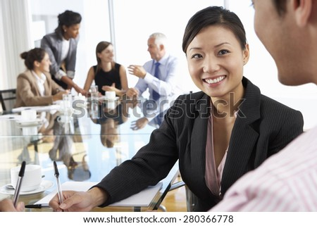 Two People Having Meeting Around Glass Table In Boardroom With Colleagues In Background - stock photo