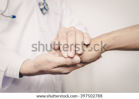 Two people holding hands for comfort. Doctor consoling relatives of patients. Doctors wear white. Focus on hands Doctor. Vintage tone. - stock photo