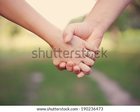 Two people holding hands outdoor. Friendship and family concept.