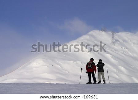Two people in front of a mountaintop - stock photo