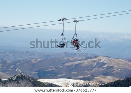 Two people in ski chairlifts on Kopaonik mountain in Serbia