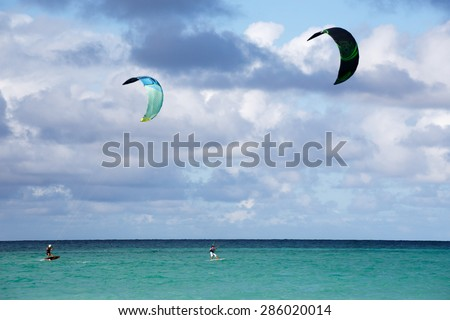 Two people kite surfing at the beach - stock photo