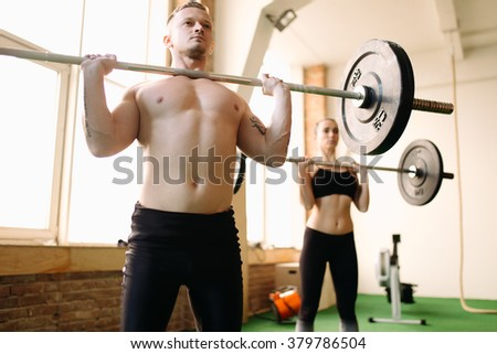 Two people lifting barbells during a gym workout - stock photo