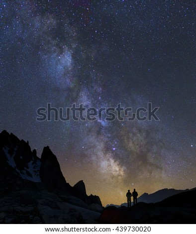 Two people looking at the night sky, with Milky Way and Galaxy, in the mountains.