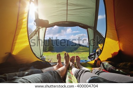 Two people lying in  tent with a view of mountains. Carpathians, Ukraine - stock photo