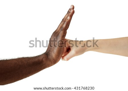Two people of different races and ethnicities holding hands in handshake expressing friendship, solidarity and cooperation. White Caucasian woman throwing a punch at the open palm of black African man - stock photo