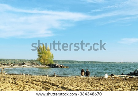 Two people on the beach Sunny autumn day - stock photo