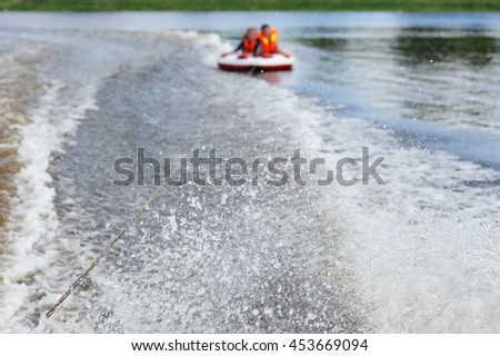 two people ride on a water tube - blurred focus and background - stock photo