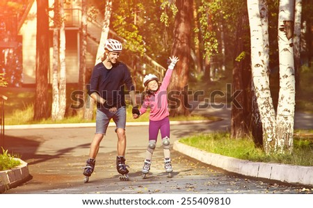 two people rollerblade. Dad with his little daughter on the skates - stock photo