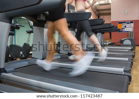 Two people running on treadmills in the gym side by side