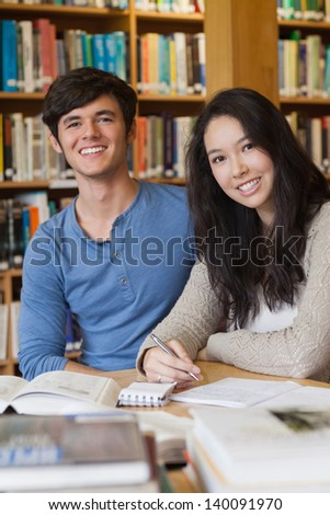 Two people sitting in a library at a desk and learning while smiling - stock photo