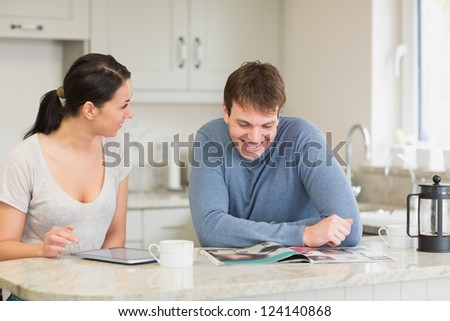Two people sitting in the kitchen having fun are reading and talking - stock photo