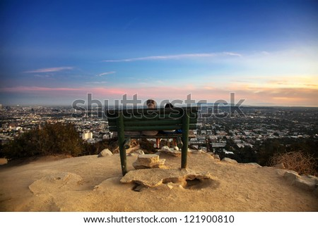 Two people sitting on a bench overlooking the city of Los Angeles, California - stock photo