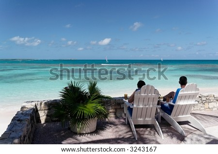 Two people sitting on canvas chairs at a beautiful caribbean terrace